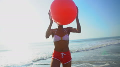Portrait of African American female having fun on holiday beach with red ball Stock Footage