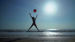 Slim African American female playing on vacation beach with red ball Stock Footage