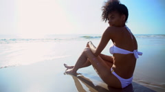Young African American woman in bikini relaxing on beach on holiday at sunshine Stock Footage