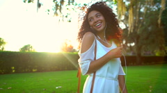 Smiling African American female listening music in the park Stock Footage