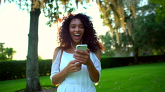 Portrait of laughing African American girl listening music in the park Stock Footage