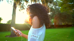 Happy young ethnic girl with afro hair dancing in the park Stock Footage