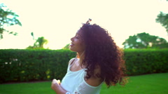Attractive laughing ethnic woman with afro hair dancing in the park Stock Footage