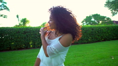 Smiling African American female in white sundress dancing in the park Stock Footage