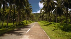 Driving on road surrounded by palm trees, Siargao, Philippines Stock Footage
