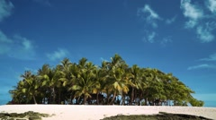 Small tropical island with palm trees, white sand and some rocks, Philippines Stock Footage