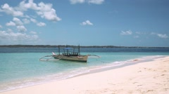 White bangca boat in clean turquoise water anchored on white sand beach Stock Footage