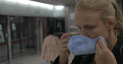 Woman putting on mask in the subway Stock Footage