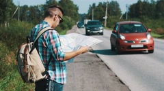 Young man with backpack hitchhiking at road in countryside. Map. Thumbing up Stock Footage