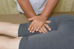 Physical therapist doing massage on woman's leg Stock Photos