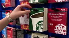 Woman picking twenty five dollars starbucks gift card inside Walmart store Stock Footage