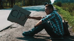 Man sit at road in countryside with cardboard plate sign city. Hitchhiking Stock Footage