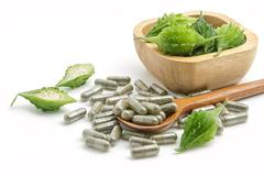 Herb pills with bitter gourd ,homeopathic medicine on white background Stock Photos