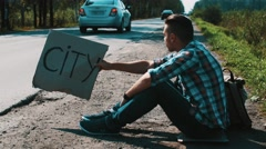 Man sit at road in countryside with cardboard plate sign city. Hitchhiking. Sun Stock Footage