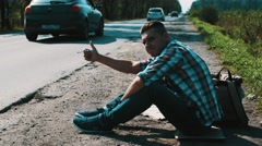 Man sit at road in countryside. Hitchhiking. Thumb up. Smoking cigarette Stock Footage