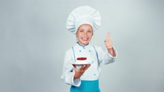 Young baker holds in her hand white plate with meringue cake and smiling Stock Footage