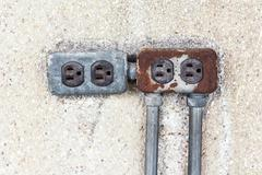 Asia plug socket on brick wall background. Risk of danger Stock Photos