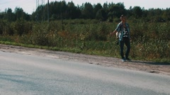 Man stay at road in countryside. Hitchhiking. Thumb up. Smoke cigarette. Travel Stock Footage