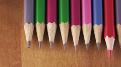 Black graphic pencils and red pencil lie in a row on a wooden surface Stock Footage