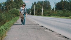Man walk along the road with cardboard plate with sign city. Hitchhiking Stock Footage