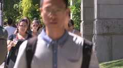 Cars pedestrians and students on campus in university district Stock Footage