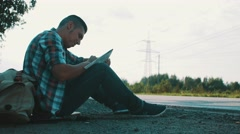 Man sit at road in countryside looking in map in hands. Hitchhiking. Laugh Stock Footage