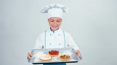 Baker holds oven-tray with three little cake and smiling at camera isolated Stock Footage