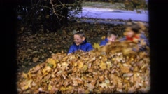 1964: three small children having fun jumping in a pile of fall leaves outside. Stock Footage