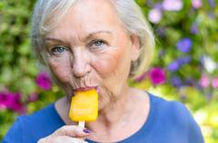 Elderly woman enjoying a refreshing iced lolly Stock Photos