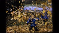 1964: two boys in blue jackets standing in a leaf pile, one throwing leaves  Stock Footage
