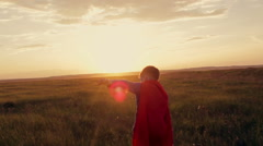 Boy superhero in a field at sunset Stock Footage