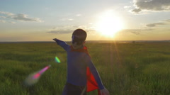Boy dressed with a Superman cape running in a field, looking into the sunset Stock Footage