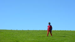 Superhero girl runs in a green field Stock Footage