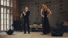 Jazz vocalist in dark dress and saxophonist in suit perform on stage. Duet Stock Footage