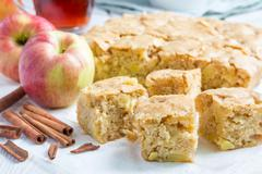 Homemade blondie (blonde) brownies apple cake, square slices on parchment Stock Photos