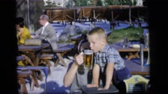 1964: a young woman giving a small boy a taste of beer from a mug CAMDEN Stock Footage