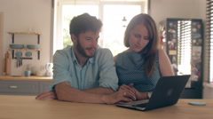 Young good-looking couple is talking at the kitchen table looking at the laptop Stock Footage