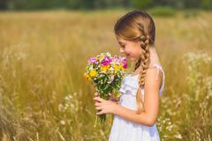Innocent girl enjoying smell of blossoms Stock Photos