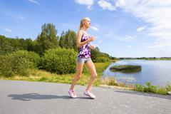 Sporty young woman runs on road along the water Stock Photos