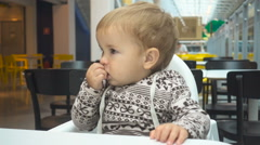 One year old child eats in a cafe. Baby boy sitting at a table in a cafe with Stock Footage