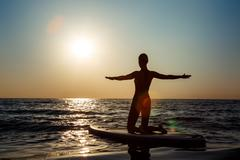 Silhouette of beautiful girl practicing yoga on surfboard at sunrise Stock Photos