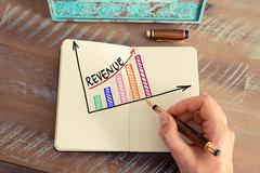 Business woman drawing a colourful REVENUE graph Stock Photos