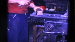 1967: man hammering object on machine PITTSBURGH, PENNSYLVANIA Stock Footage