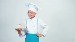 Portrait young baker holds piece of cheesecake and gives you it. Isolated Stock Footage