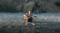 The guy playing the guitar at sunset on the beach. Slowmotion Stock Footage