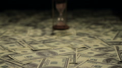 Hourglass standing on american hundred dollar bills. Dolly slider shot Stock Footage