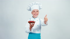 Young baker holds sponge cake with raspberries standing. Thumb up. Ok Stock Footage
