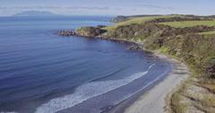Aerial over beach and calm ocean at Tawharanui, auckland Stock Footage