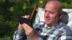 Smiling People Siting in a Chair in His Garden Use Mobile Phone Web Connection. Stock Footage