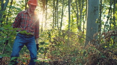Logger with axe walking near tree trunk. RAW video record Stock Footage